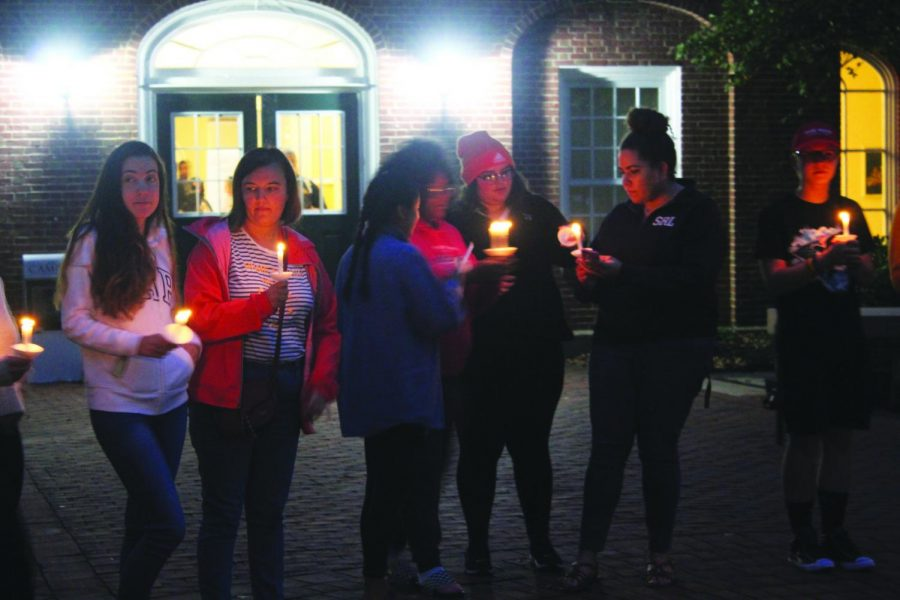 Students light one another's candles at the 9/11 Vigil in Brooks Circle on Tuesday, Sept. 11, 2018.