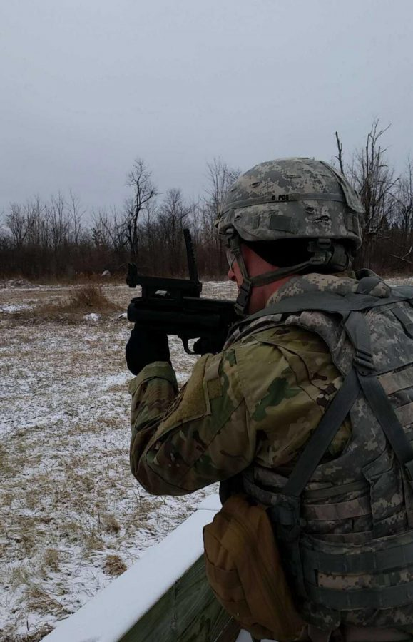 Aaron Burnside, '22, fires a rifle in fatigues. Burnside served in the army for five years.