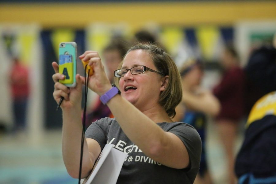 Becky Dawson, assistant volunteer swimming and diving coach, takes a photo on her cellphone while coaching the Allegheny team. Dawson also serves as a faculty athletic representative and teaches classes at Allegheny.