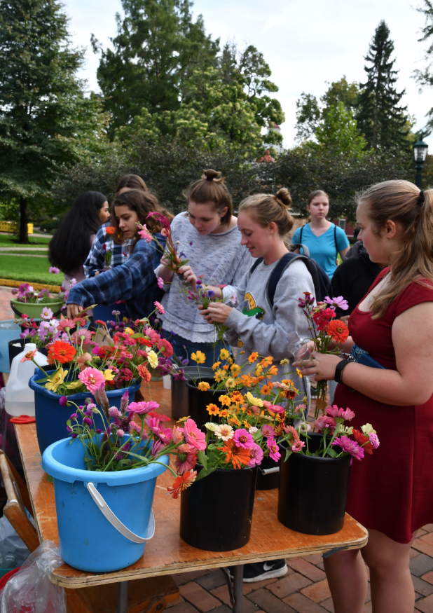 Students+create+their+own+bouquets+of+flowers%2C+grown+by+Nancy+Schultz+and+her+daughter%2C+Lorraine+Sillman%2C+of+Saegertown%2C+on+Sept.+26%2C+2018%2C+at+the+community+market+next+to+the+Carrden.++