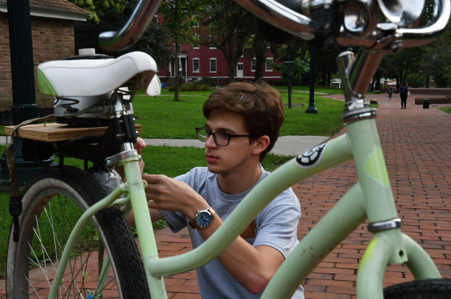 Ray Marszalek, '21, of  the Allegheny College Bike Share, sets up a stationary blender bike at the DeHart community market. Bike Share students offered applesauce made from the stationary blender bike and a mobile blender bike.