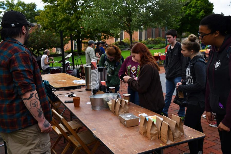 Michael Reed, owner of Tarot Bean Roasting Co. on Chestnut Street, tells students about coffee for sale at the DeHart community market.