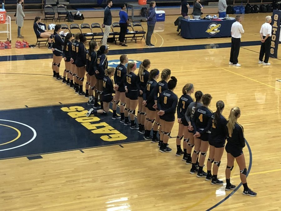 First-year volleyball student-athlete Claire Klima, '22, kneels in her team lineup during the national anthem at a home game on September 22, 2018.