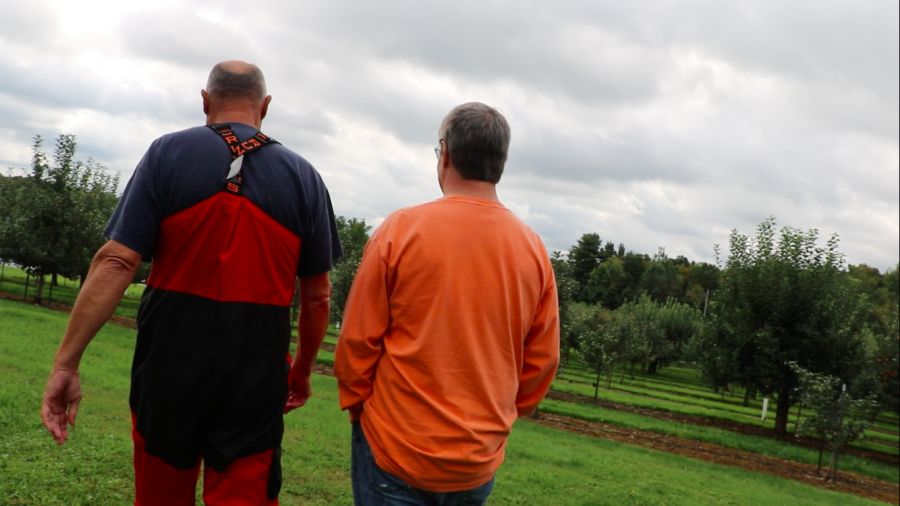 Jeff Boswell and Jeff Davenport walk through the orchard on Sept. 29, 2018.