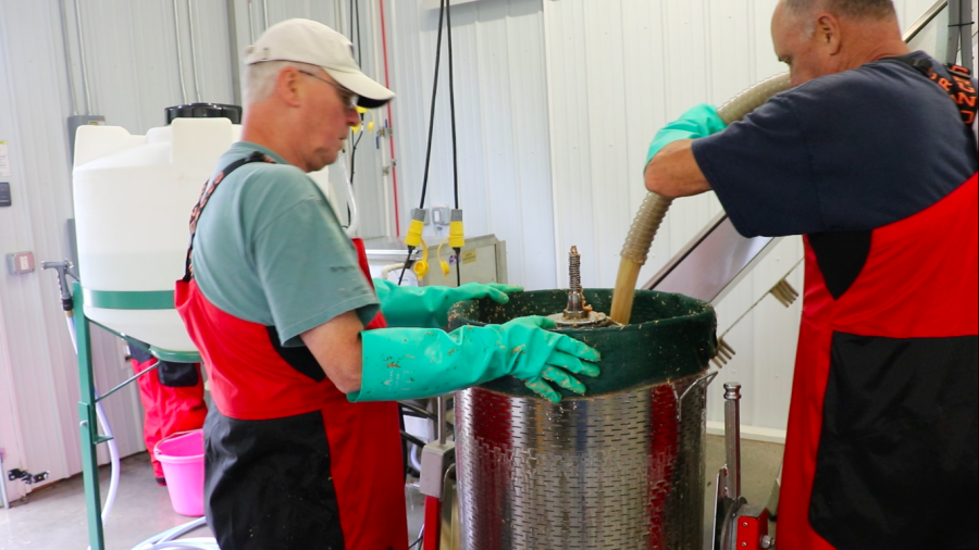 Jack Boss and Jeff Davenport press cider in the production room of the farm's cider barn on Sept. 29, 2018. Farm manager Rosie Holeva and owner Jeff Boswell took turns filling gallon jugs with finished cider.