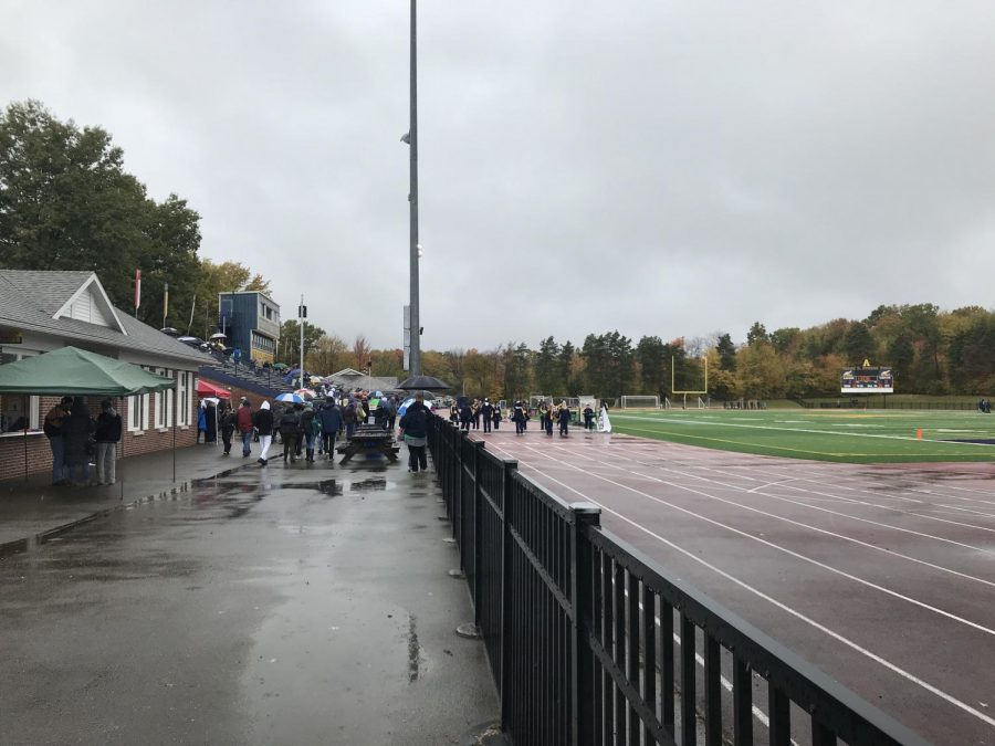 Crowds gather near the sidelines in rain gear at Robertson Athletic Complex.