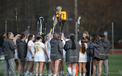 The women's lacrosse team huddles by the sideline during its game against John Carroll University at Frank B. Fuhrer Field on March 27, 2019.