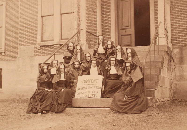 """A group of Allegheny College students, dressed as nuns, sit on the steps of Hulings Hall in 1889. A sign reads """"Convent/No boys allowed/Coeducation is a failure"""" in protest of the college's sexist rules and restrictions that governed its newly enrolled female students."""