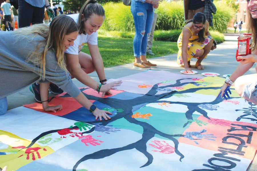 Rhiannon King, '20, Mary Allen, '22, and Marisol Santa Cruz, '20, make hand prints on a banner during the Climate Strike on Friday, Sept. 20, 2019, outside the Henderson Campus Center.
