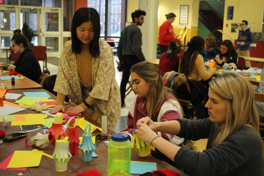 Miharu Koh, 20, assists students in constructing their custom lanterns during the Lantern Festival celebration in the Henderson Campus Center lobby on Feb. 12, 2020.