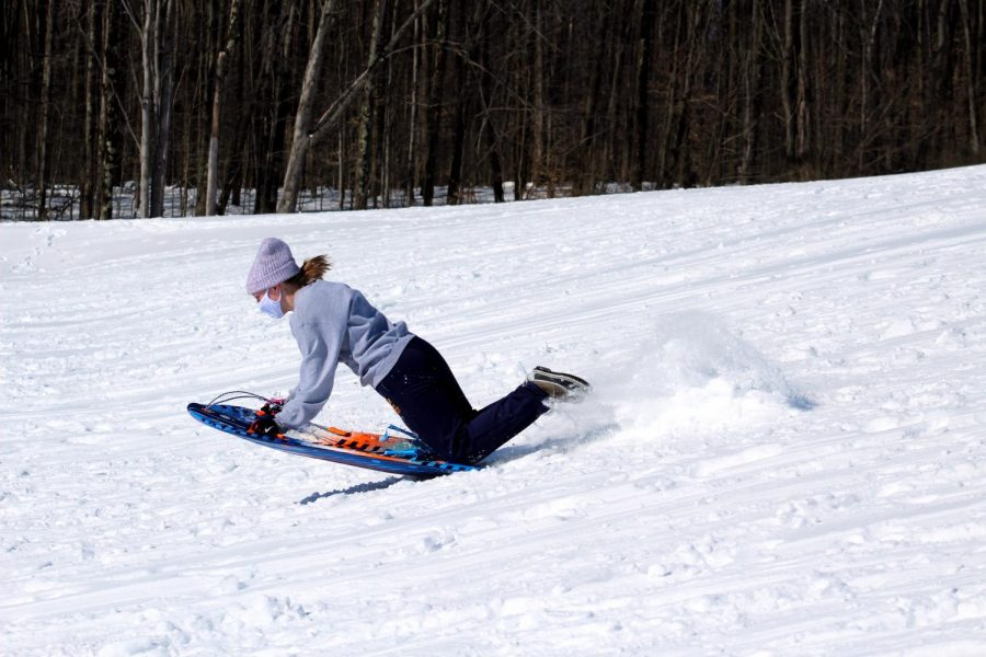 Becca Winton, '23, sticks the landing after going off a small ramp students built at the sledding event