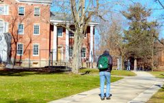 A student walks in front of the east wing of Bentley Hall