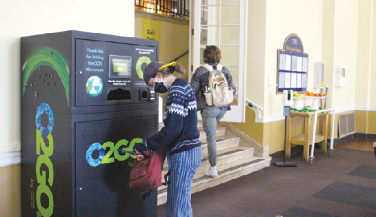 Student returns green box in Brooks Dining Hall.