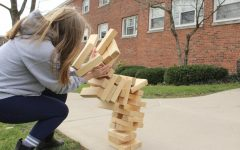 Becca Winton, '23, takes the brunt of a giant Jenga tower's collapse at an Egg Hunt hosted in front of Schultz Hall on Saturday, April 3.