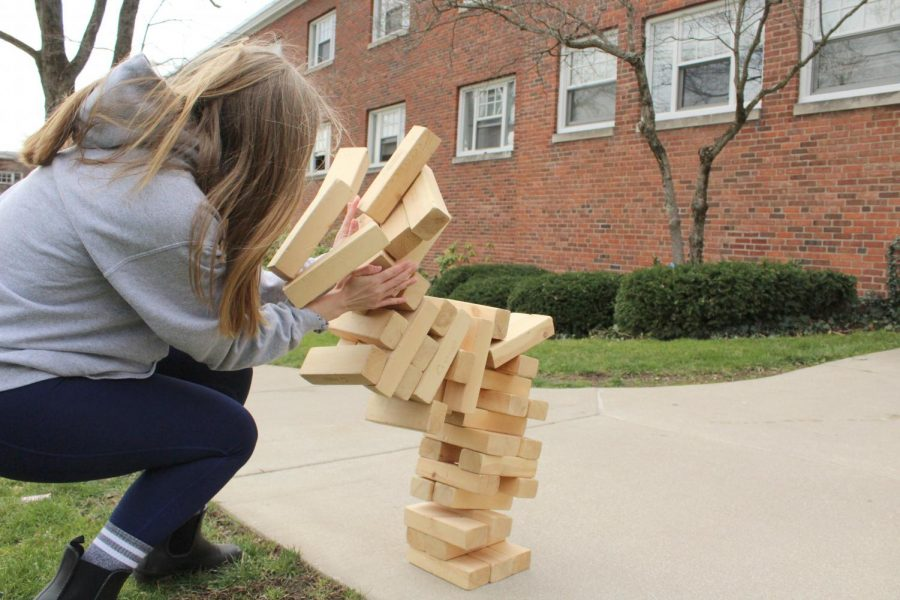 Becca+Winton%2C+%E2%80%9923%2C+takes+the+brunt+of+a+giant+Jenga+tower%E2%80%99s+collapse+at+an+Egg+Hunt+hosted+in+front+of+Schultz+Hall+on+Saturday%2C+April+3.