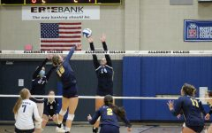 Middle Hitter Dagney Javes, '25' spikes the ball across the net at the Titans.
