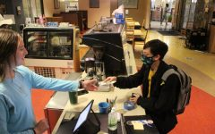 """Mary Allen, '22 takes payment from Charlie Schwartz, '25, who purchased the first coffee of the year at 8:25am on Monday, Sept. 13. Allen had always wanted to volunteer, but had not followed through until this year. """"I just thought it would be cool,"""" Allen said."""