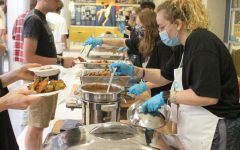 Syd Hammerman, '25 (right), serves a vegan attendee of Wingfest in the Campus Center on Sept. 19.