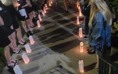 Attendees honor victims of domestic violence with candles during a vigil at the Ford Chapel on Oct. 16.