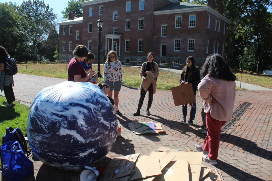 Students+collect+signs+next+to+a+giant+inflatable+globe+that+Candace+Burkhammer%2C+%E2%80%9922%2C+co-president+of+SEA%2C+brought+to+the+event.