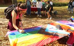 """Furbish signs a """"Progress"""" Pride flag as face-painting continues in the background. There are several variations to the traditional rainbow Pride flag that have been developed, including the six color (red, orange, yellow, green, blue, and purple), the Philadelphia flag, which adds black and brown to the six colors, and the """"Progress"""" flag, inspired by the flag of South Africa."""