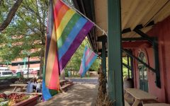"""The """"Philadelphia"""" pride flag hangs at one end of the Market House, with a transgender pride flag hanging in the background."""